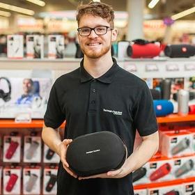 Junger Mann steht im Markt und verkauft Bluetoothbox