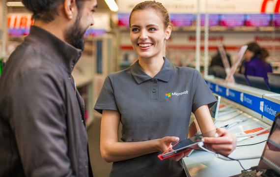 Junge Dame am Microsoft Windows Stand in einem Gespräch mit einem Kunden