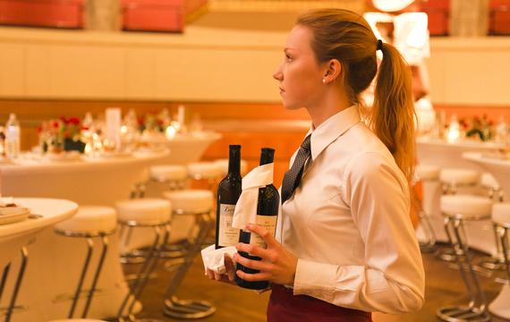 Junge Mitarbeiterin schenkt Wein bei Gastro-Event aus