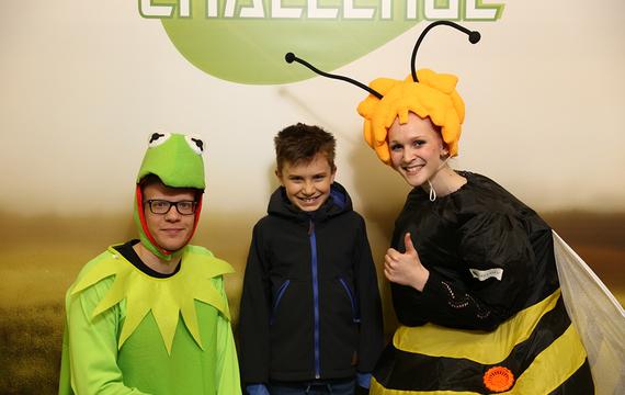 2 Personen verkleidet als Frosch und Biene mit Kind