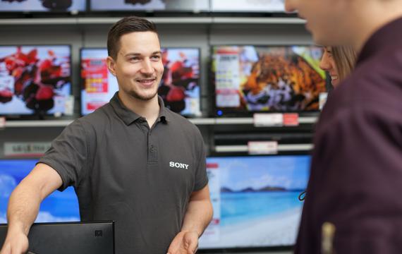 Junger Mitarbeiter berät Kunden über Sony-Produkt