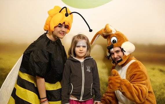 Personen verkleidet als Hase und Biene mit Kind