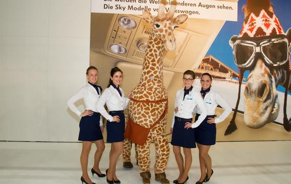 Junge Damen mit einer Giraffe bei der Vienna Autoshow für VW