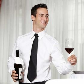 Junger dunkelhaariger Mann mit Hemd und Krawatte bietet Gast ein Rotweinglas an.