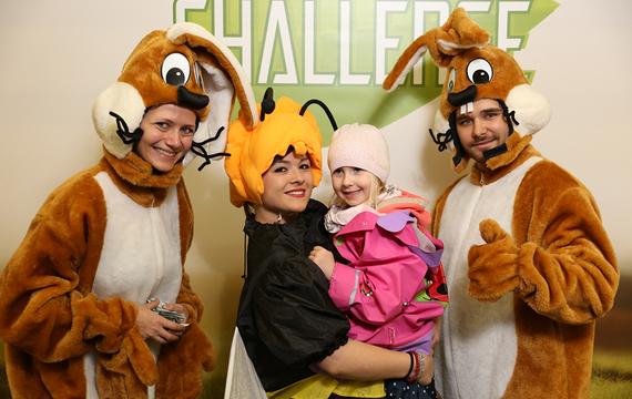 Personen verkleidet als Hasen und Biene mit Kind im Arm