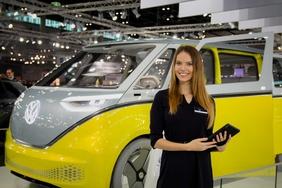 Junge Dame mit Tablet steht vor dem neun elektrischen VW Bus.