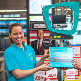 Mitarbeiterin übergibt Produkt an Kundin