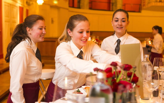 Junge Mitarbeiterinnen bereiten Tisch bei Gastro-Event vor