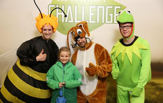 Personen verkleidet als Biene, Hase und Frosch mit Kind