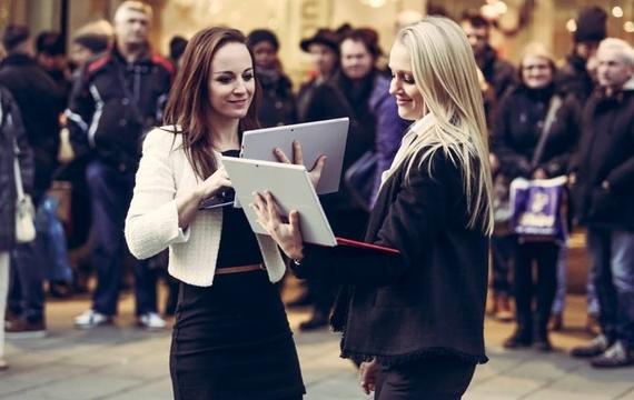 Zwei junge Damen stehen sich mit Windows Surface gegenüber