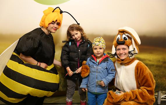 2 Personen verkleidet als Biene und Hase mit 2 Kindern