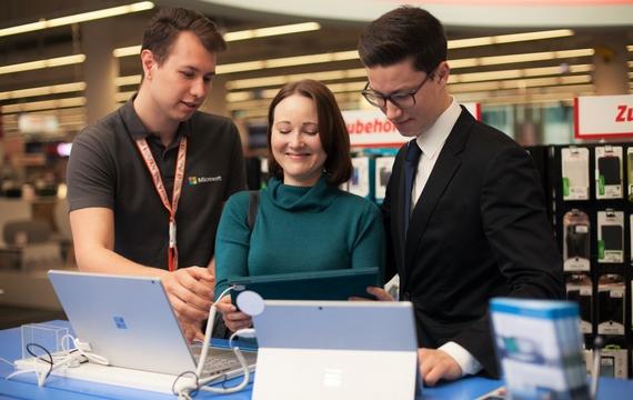 Junger Herr am Microsoft Windows Stand in einem Gespräch mit einem Kunden