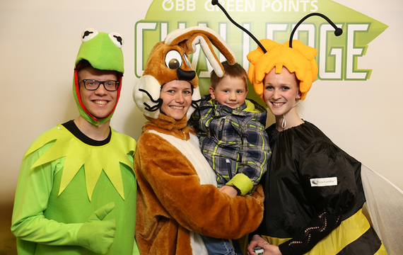 Personen verkleidet als Frosch, Hase und Biene mit Kind
