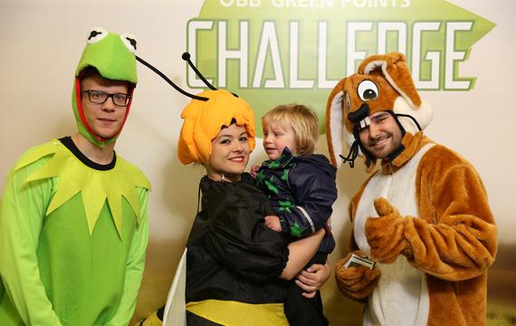 Personen verkleidet als Frosch, Biene und Hase mit Kind