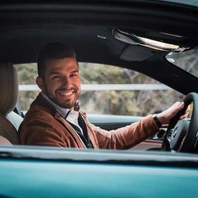 Junger Mann sitzt in einem BMW und lächelt.