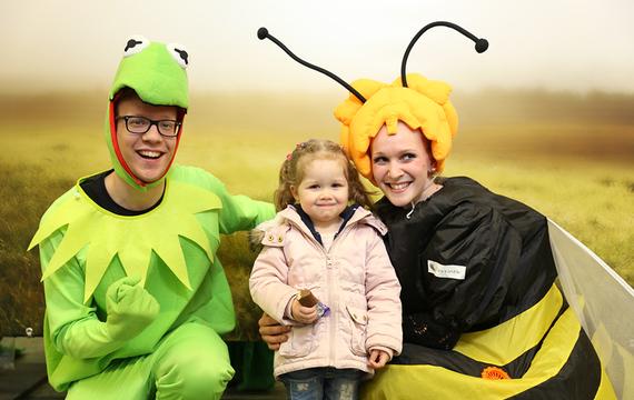 Personen verkleidet als Biene und Frosch mit Kind