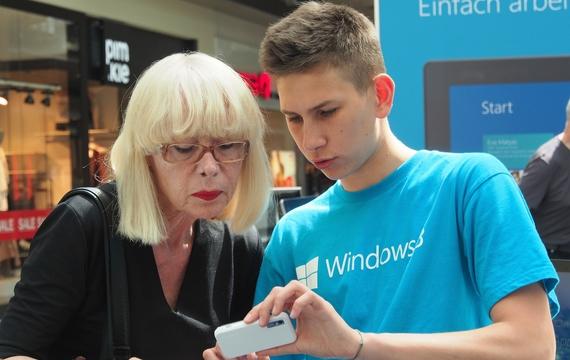 Mitarbeiter zeigt älterer Dame Windows Mobile