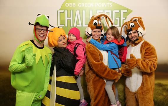 Personen verkleidet als Frosch, Biene und Hasen mit Kindern