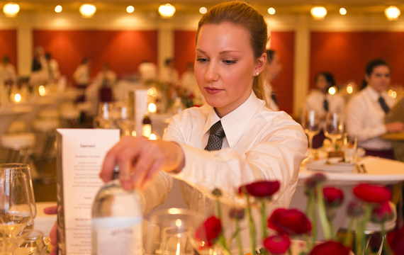 Junge Mitarbeiterin bereitet Tisch bei Gastro-Event vor