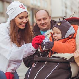 Junge Mitarbeiterin verteilt Kostprobe an Kind