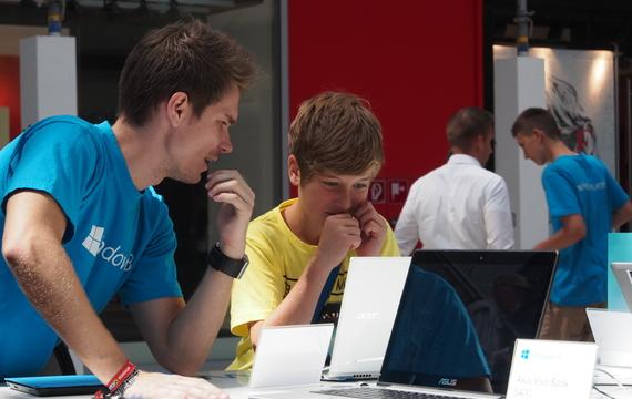 Mitarbeiter zeigt jungen Kunden das neue Windows Microsoft
