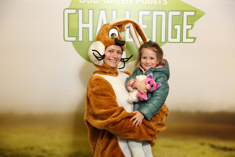 Frau verkleidet als Hase mit Kind im Arm
