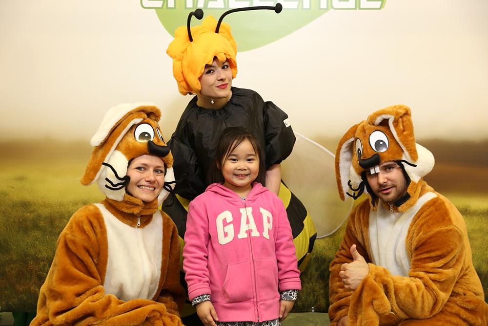 Personen verkleidet als Biene und Hasen mit Kind
