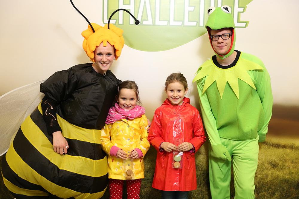 Personen verkleidet als Biene und Froshc mit Kindern